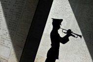 A Philippine soldier blows his bugle along the halls displaying engraved names of soldiers fallen during the World War II at the commemoration of US Memorial Day at the Manila American Cemetery in Fort Bonifacio, Manila in 2010. President Barack Obama's administration pledged to reach out to Filipinos seeking payments for World War II service after complaints from veterans over denied claims