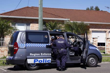 Police talk as they guard a house that was involved in pre-dawn raids in western Sydney