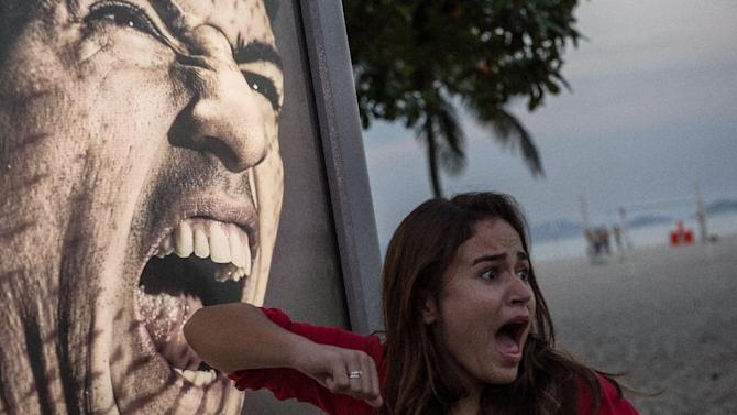 A tourist jokes in front of an advertisement with the portrait of Uruguay's forward Luis Suarez at Copacabana beach in Rio de Janeiro, Brazil, on June 26, 2014
