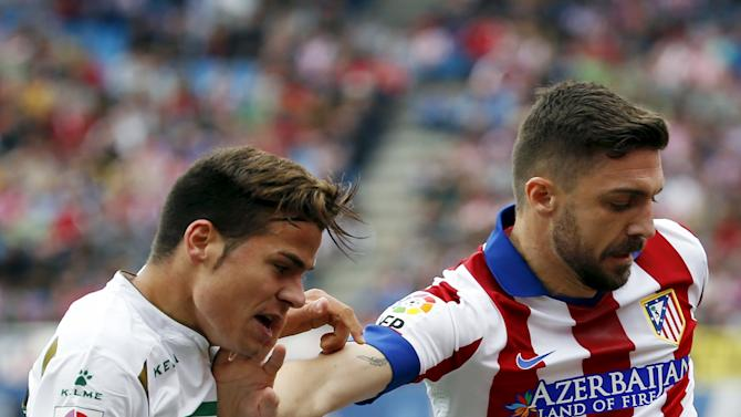 Atletico Madrid's Siqueira fights for the ball with Elche's Samuel during their Spanish first division soccer match at Vicente Calderon stadium in Madrid