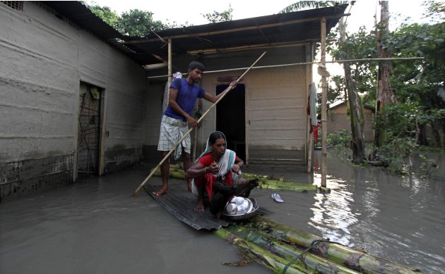 Flood-affected residents use a temporary raft to move their belongings to safer places in front of their submerged hut at Himalua village