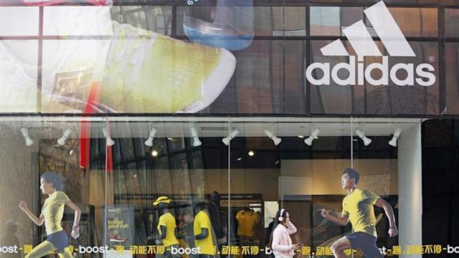 A woman walks past an Adidas shop at a shopping district in Beijing March 25, 2013. REUTERS/Kim Kyung-Hoon