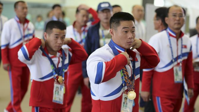 North Korea's Om and Kim adjust their gold medals as they arrive for a news conference at the 17th Asian Games in Incheon