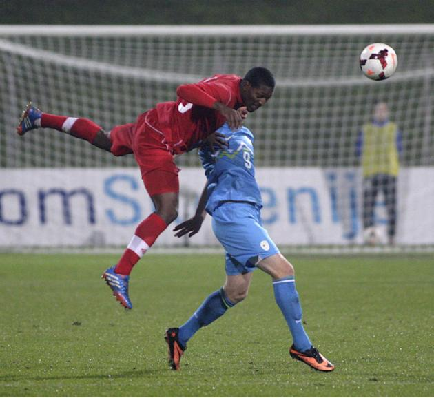 Canada's Doneil Henry, left, heads a ball in front of Slovenia's Jasmin Kurtic by during a friendly soccer match between Slovenia and Canada, in Celje, Slovenia, Tuesday, Nov. 19, 2013