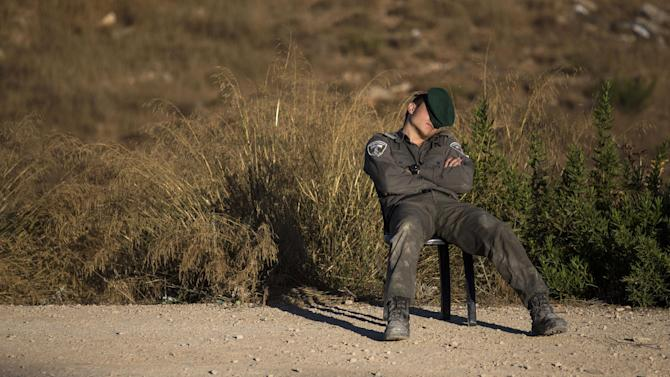 """An Israeli border police officer sleeps at the Jewish settlement of Beit El, near the West Bank town of Ramallah, Wednesday, July 29, 2015.  The Israeli Prime Minister's office said Wednesday it has approved the """"immediate construction"""" of 300 housing units in the West Bank settlement of Beit El. The announcement came amid a standoff in Beit El, where Israeli settlers clashed with Israeli forces as authorities began to demolish a contested West Bank settlement housing complex after Israel's Supreme Court ruled Wednesday that it must be demolished. (AP Photo/Tsafrir Abayov)"""