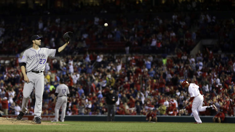 Colorado Rockies starting pitcher Jon Garland, left, gets a new ball after giving up a solo home run to St. Louis Cardinals' Carlos Beltran, right, during the third inning of a baseball game on Friday, May 10, 2013, in St. Louis. (AP Photo/Jeff Roberson)