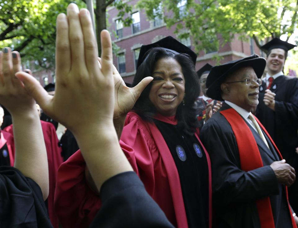 Oprah Winfrey receives high-fives from graduates as she walks with Prof. Henry Louis Gates during the procession at Harvard University commencement ceremonies in Cambridge, Mass., Thursday, May 30, 2013. (AP Photo/Elise Amendola)