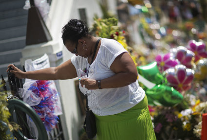 Terri Barr, of Columbia, S.C., stands silently against a fence while visiting a sidewalk memorial for the shooting victims in front of Emanuel AME Church. (AP/David Goldman)