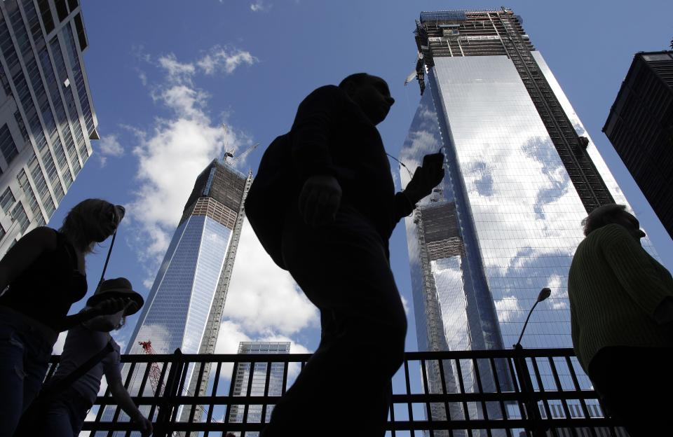 Visitors to the National September 11 Memorial walk below the rising towers 1 World Trade Center, left, and 4 World Trade Center, Monday, Sept. 10, 2012 in New York. Tuesday will mark the eleventh anniversary of the attacks of Sept. 11, 2001. (AP Photo/Mark Lennihan)