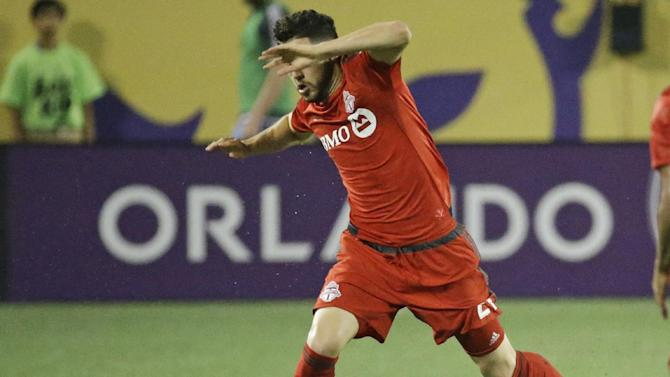 Toronto FC's Jonathan Osorio, left, rumps over Orlando City's Kevin Molino, right, as he moves the ball during the second half of an MLS soccer game, Sunday, April 26, 2015, in Orlando, Fla. Toronto won 2-0. (AP Photo/John Raoux)