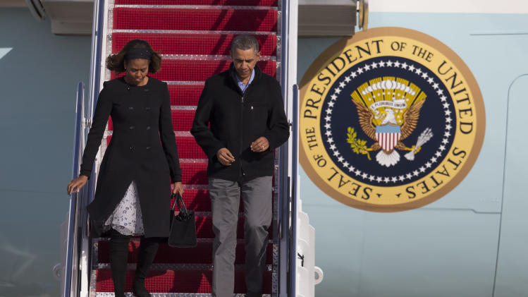 President Barack Obama and first lady Michelle Obama step off Air Force One after arriving at Andrews Air Force Base after spending the weekend in Key Largo, Fla., on Sunday, March 9, 2014, in Andrews Air Force Base, Md. (AP Photo/ Evan Vucci)