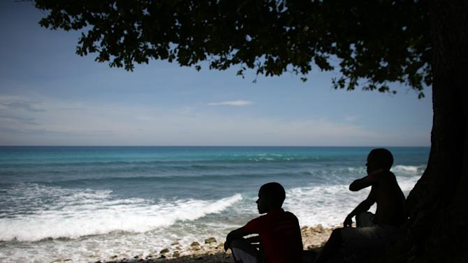 Two men look out at the beach in Barahona, Dominican Republic, Thursday, Aug. 23, 2012. Puerto Rico and the U.S. Virgin Islands braced for torrential rains on Thursday as Tropical Storm Isaac whipped up waves as high as 10 feet (3 meters) in the Caribbean and threatened to become a hurricane that could take a shot at Florida just as Republicans gather for their national convention.  (AP Photo/Ricardo Arduengo)