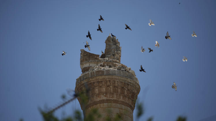 FILE - Birds fly over the destroyed minaret of a mosque in the northern town of Ariha, on the outskirts of Idlib, Syria, Sunday, June 10, 2012. (AP Photo/Khalil Hamra, File)