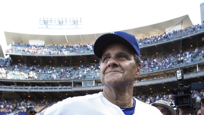 FILE - In this Oct. 3, 2010 file photo, Los Angeles Dodgers manager Joe Torre watches a video tribute during his farewell ceremony after a baseball game with the Arizona Diamondbacks,  in Los Angeles. Torre has resigned as Major League Baseball's executive vice president for baseball operations to join a group trying to buy the Los Angeles Dodgers. (AP Photo/Jae C. Hong, File)