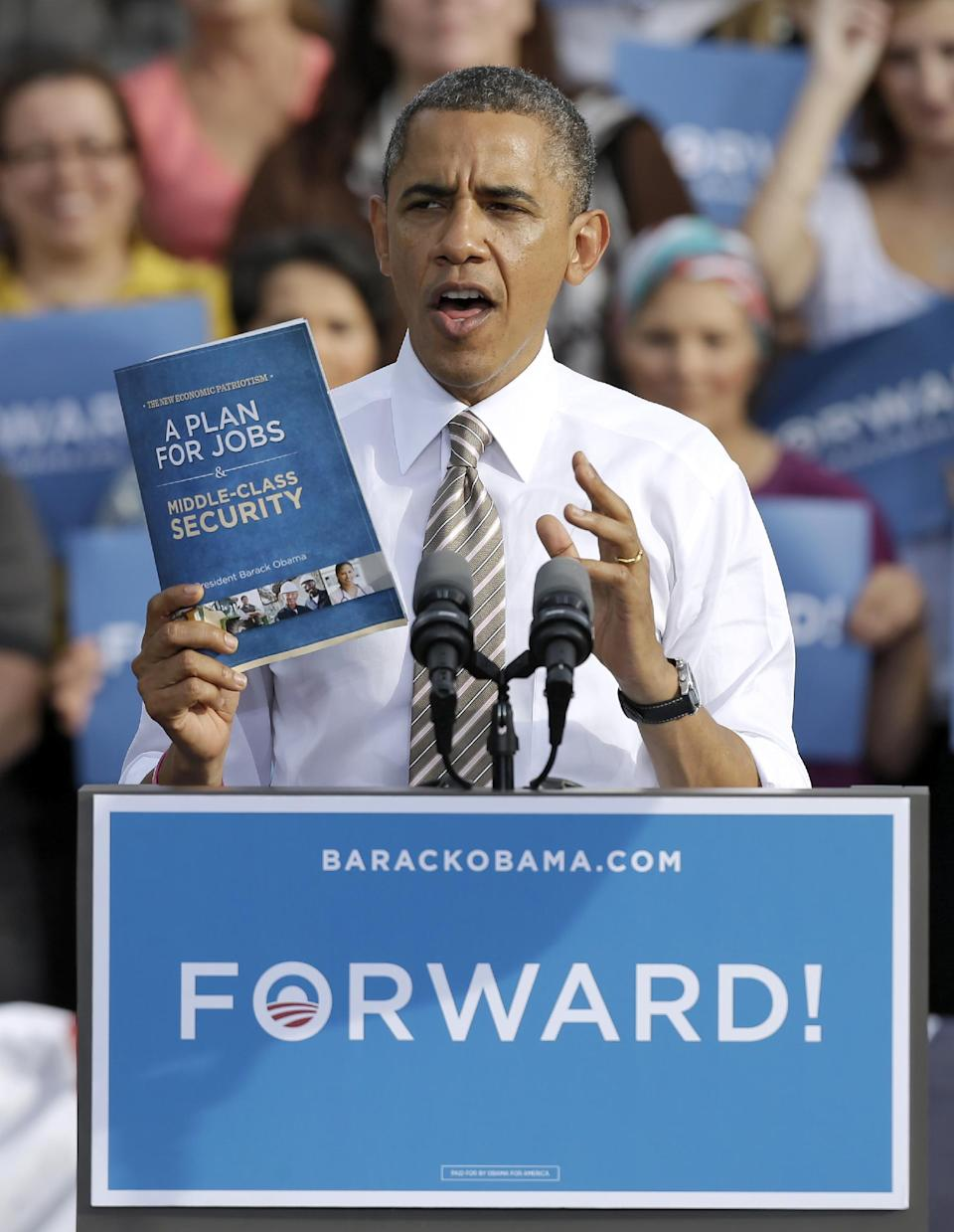 President Obama holds up his jobs plans booklet while speaking at a campaign stop, Thursday, Oct. 25, 2012, in Tampa, Fla. (AP Photo/Chris O'Meara)