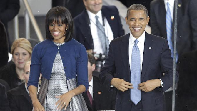 FILE - This Jan. 21, 2013 file photo shows President Barack Obama and first lady Michelle Obama watching the Inaugural parade in the reviewing stand in front of the White House on Pennsylvania Ave., in Washington. Nobody would call bangs a new trend, but when the first lady's involved, things take on more significance. In fact, President Barack Obama did call his wife Michelle's new hairdo the most significant event of his second inauguration. (AP Photo/Gerald Herbert, File)