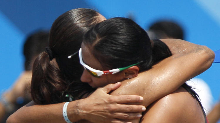 Mexico's Mayra Garcia, left, and teammate Bibiana Candelas embrace after winning a women's beach volleyball semifinal match against the United States at the Pan American Games in Puerto Vallarta, Mexico, Thursday, Oct. 20, 2011. (AP Photo/Ariana Cubillos)