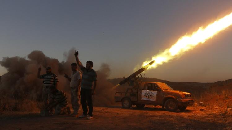 Free Syrian Army fighters react while launching a rocket towards Hama military airport that is controlled by forces loyal to Syria's President Assad, in the Hama countryside
