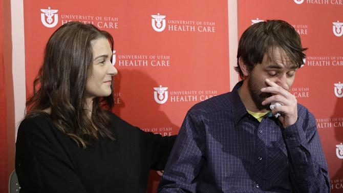 Avalanche survivor, Elisabeth Malloy looks on as skiing partner and initial rescuer Adam Morrey tears up as he discusses their avalanche ordeal during a news conference at the University of Utah Health Care's Burn Center Wednesday, Jan. 16, 2013, in Salt Lake City. Malloy suffered frost bite in her toes and fingers, but emerged otherwise unscathed from Saturday's near-death encounter in the mountains east of Salt Lake City. She survived thanks to her boyfriend, Adam Morrey, avalanche rescue beacons, a skier that wandered by and avalanche rescue teams.  (AP Photo/Rick Bowmer)