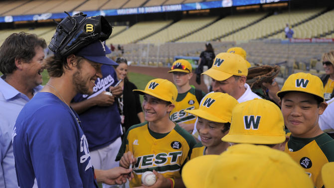 Los Angeles Dodgers starting pitcher Clayton Kershaw, left, signs balls for members of the Little League-champion Ocean View team prior to the Dodgers' baseball game against the San Francisco Giants, Thursday, Sept. 22, 2011, in Los Angeles. (AP Photo/Mark J. Terrill)