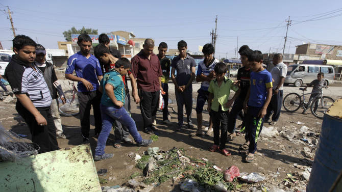 People gather at the scene of a bomb attack in the neighborhood of Bawiya in eastern Baghdad, Iraq, Saturday, Oct. 27, 2012. A bombing near a playground and other insurgent attacks killed 18 people including several children in Iraq on Saturday, police said. (AP Photo/Khalid Mohammed)