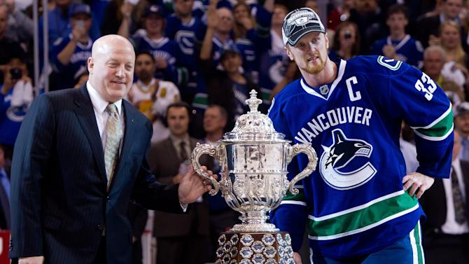 Vancouver Canucks' Henrik Sedin, right, of Sweden, accepts the Clarence S. Campbell trophy from NHL Deputy Commissioner Bill Daly after defeating the San Jose Sharks in the second overtime period of game 5 of the NHL Western Conference Final Stanley Cup playoff hockey series in Vancouver, British Columbia, on Tuesday May 24, 2011. Vancouver won the series 4 games to 1 and advances to the Stanley Cup Final. (AP Photo/THE CANADIAN PRESS/Darryl Dyck)