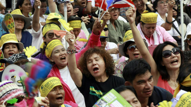 Anti-government protesters chant slogans during a rally outside a park in Bangkok, Thailand Sunday, Aug. 4, 2013. About 1,500 people took part in the rally calling Prime Minister Yingluck Shinawatra to withdraw the amnesty bill from parliament. The Thai capital is bracing for possible unrest this week, with street protests expected over moves in parliament that could eventually lead to a pardon for ousted Prime Minister Thaksin Shinawatra. (AP Photo/Apichart Weerawong)