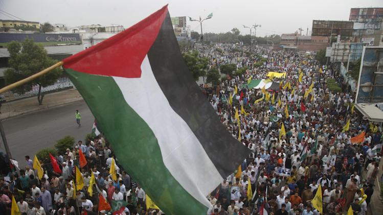 A Palestinian flag flies over Pakistani protesters marching to express solidarity with Palestinians, during a rally marking Al-Quds (Jerusalem) Day in Karachi, Pakistan, Friday July 25, 2014. Al-Quds Day is the last Friday of the Muslim holy month of Ramadan declared by the Iranian late spiritual leader Ayatollah Ruhollah Khomeini as an international day of struggle against Israel and for the liberation of Jerusalem. (AP Photo/Shakil Adil)