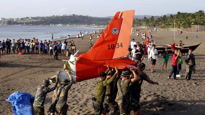 Soldiers carry the tail of an ill-fated Philippine Air Force Italian made light aircraft SIAI-Marchetti SF260 that crashed in the sea off the coast of Nasugbo, Batangas south of Manila