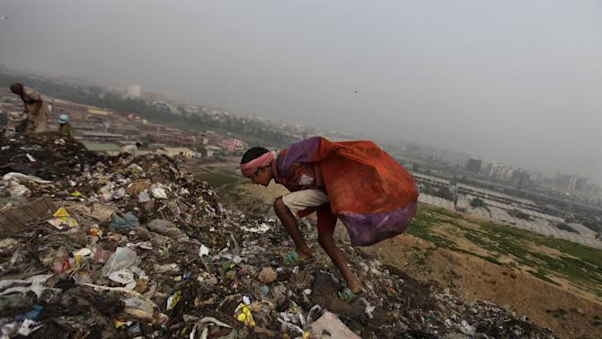 In this Sept. 13, 2012 photograph, a young Indian ragpicker loses his balance as he goes about the routine of searching through garbage for reusable garbage at a dumping ground on the outskirts of New Delhi, India. Those whose survival depends on this gray market in trash fear their lives are about to be upended. Because where they see money in those mountains of garbage, the New Delhi government sees electricity. Desperate for cheap energy, the Delhi government is experimenting with power plants fueled by garbage. One plant is now running on a trial basis and two more are under construction. (AP Photo/Altaf Qadri)