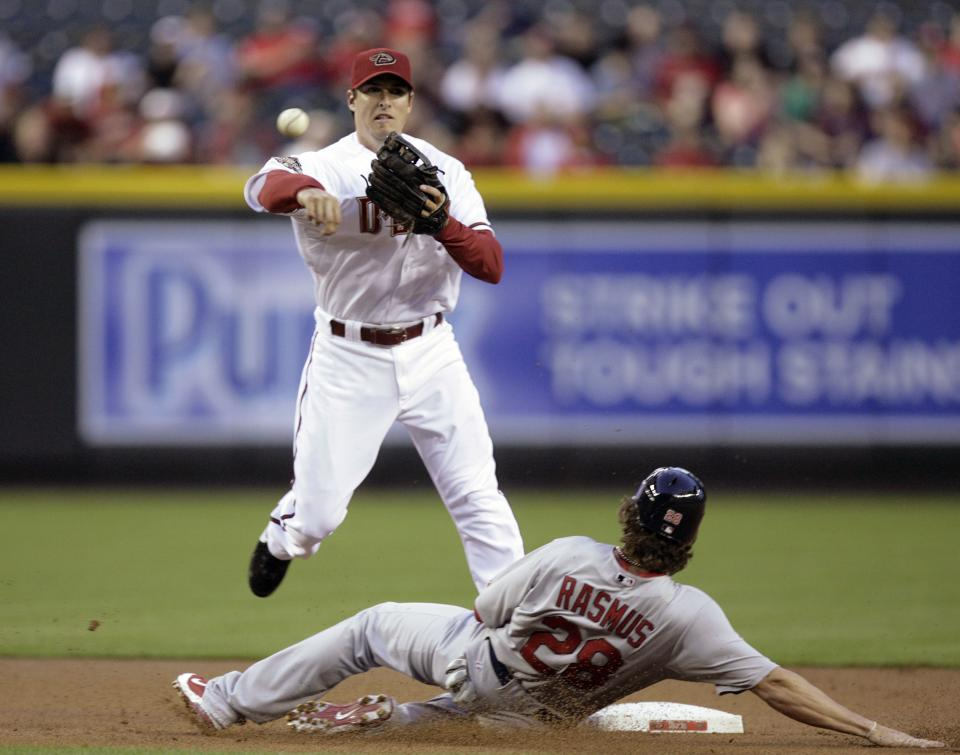 Arizona Diamondbacks shortstop Stephen Drew, top, avoids the slide by St. Louis Cardinals' Colby Rasmus, bottom, as he throws to first to complete a double play on a ball hit byAlbert Pujols in the first inning of a baseball game Monday, April 11, 2011, in Phoenix. (AP Photo/Paul Connors)