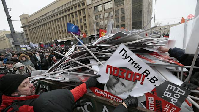 """People throw portraits brought to the rally in the garbage during a protest rally in Moscow, Russia, Sunday, Jan. 13, 2013, with the portrait of Russian President Vladimir Putin in the center. Thousands of people are gathering in central Moscow for a protest against Russia's new law banning Americans from adopting Russian children. They carry posters of President Vladimir Putin and members of Russia's parliament who overwhelmingly voted for the law last month. The posters have the word """"Shame"""" written in red over the faces and proclaim that Sunday's demonstration is a """"March Against the Scum"""" who enacted the law. (AP Photo/Ivan Sekretarev)"""