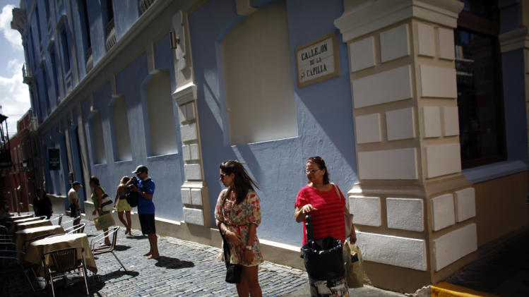 People walk through a cobblestone street in Old San Juan, Puerto Rico, Jan. 24, 2013. In recent years, Old San Juan has been on an upswing; its cobblestone streets are cleaner and livelier. New stores, restaurants and coffee shops have opened and many of the old homes have been restored. It's a working city, home to the governor's office and mansion _ said to be the oldest in the western hemisphere _ as well as other government offices and an increasing number of professional firms. It's also become an increasingly busy cruise ship port and outlet and luxury goods shops have proliferated in response. (AP Photo/Ricardo Arduengo)