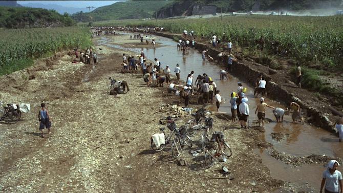 In this Aug. 13, 2012 photo, North Koreans try to rebuild the banks of a washed out riverbed near their corn fields which were damaged by July flooding, in Songchon County, North Korea. (AP Photo/David Guttenfelder)