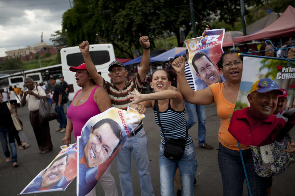 Supporters of Venezuela's President Hugo Chavez cheer on fellow supporters driving past in a campaign caravan in Caracas, Venezuela, Friday, Sept. 28, 2012. Venezuela's presidential election is scheduled for Oct. 7.  (AP Photo/Rodrigo Abd)