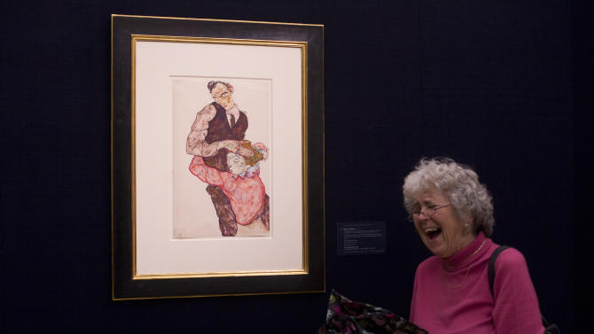 """A woman reacts to her photograph being taken next to a work on paper by Egon Schiele entitled """"Liebespaar (Selbstdarstellung mit Wally)"""" """"Lovers ( Self Portrait with Wally)"""" 1914-15, at Sotheby's auction house during a press preview in London, Thursday, Jan. 31, 2013.  The work is estimated to sell for some 6.5-8.5 million pounds ( US$ 10.4-13.6 million, euro 8-10.5 million) at auction in London on Feb. 5. (AP Photo/Alastair Grant)"""