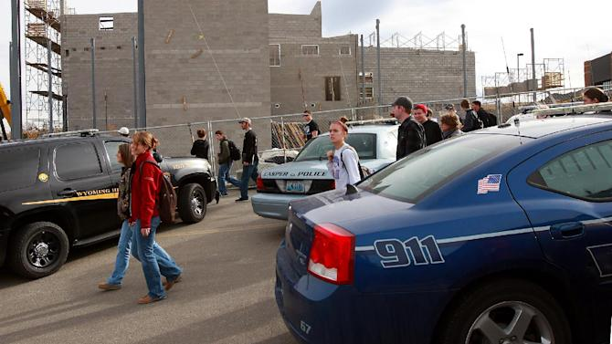 Casper College students try to reach their vehicles after the campus was released from lockdown due to a reported homicide on Friday morning, Nov. 30, 2012, in Casper, Wyo. At least one person was killed and another was wounded Friday in an attack at Casper College, a community college in central Wyoming. It happened around 9 a.m., said school spokesman Rich Fujita.  (AP Photo/Casper Star-Tribune, Alan Rogers) MANDATORY CREDIT  TRIB.COM