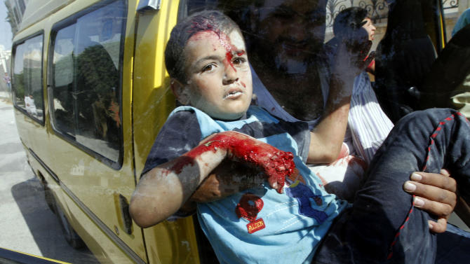 An injured Syrian boy arrives at a field hospital after an air strike hit homes in the town of Azaz, on the outskirts of Aleppo, Syria, Wednesday, Aug. 15, 2012. (AP Photo/ Khalil Hamra)