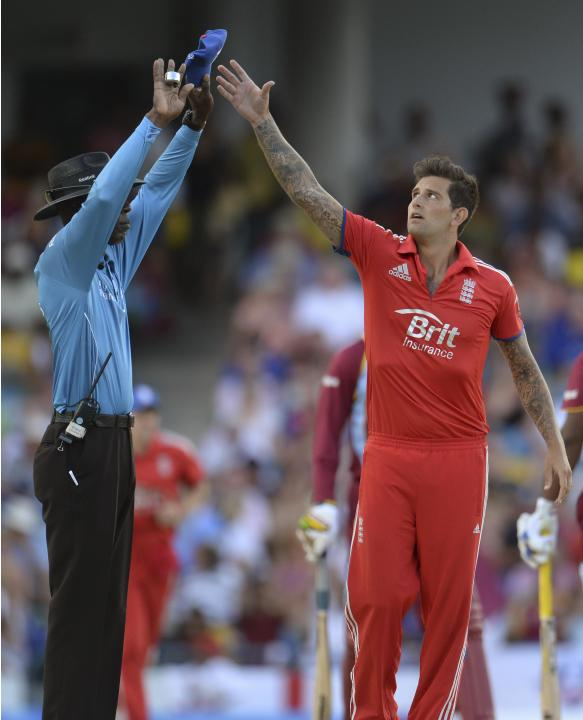 England's Dernbach reaches for his cap from umpire Nero after a six hit by West Indies' Chris Gayle during the second T20 international cricket match in Barbados