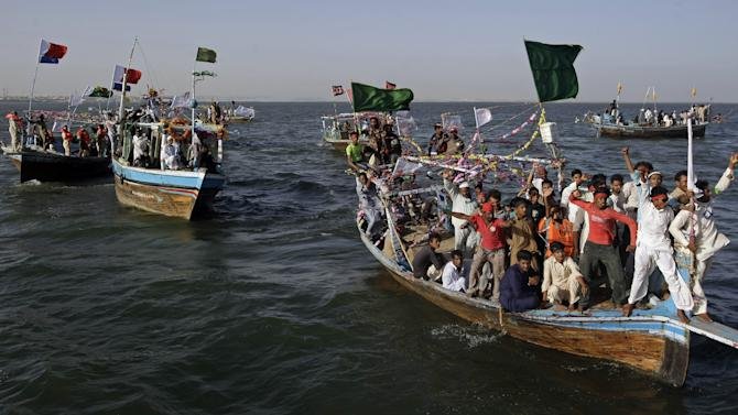 In this Friday, May 3, 2013 photo, supporters for an independent  Pakistani election candidate participate in a waterborne rally to highlight the challenges faced by their embattled fishing community in the Arabian Sea off the coast of Karachi, Pakistan. Backers of independent political candidate Haji Usman Ghani took to the water Friday on a flotilla of fishing boats in the run up to the  May 11, 2013 vote which will mark the first time that a democratically elected civilian government has finished a full term and handed over power to another such government in Pakistan. (AP Photo/Fareed Khan)