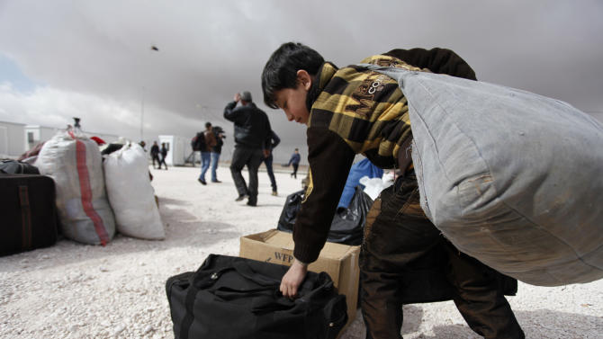 A newly-arrived Syrian refugee boy carries his family's belongings to the new Jordanian Emirati refugee camp, Mrajeeb al-Fhood, in Zarqa, Jordan, Wednesday, April 10, 2013. A second camp for Syrian refugees has opened in Jordan as more Syrians flee the civil war at home. The Jordanian-Emirati camp, is the first funded by the United Arab Emirates and run by its Red Crescent Society in Jordan to  assist families, single women, the disabled, and elderly. (AP photo/Mohammad Hannon)