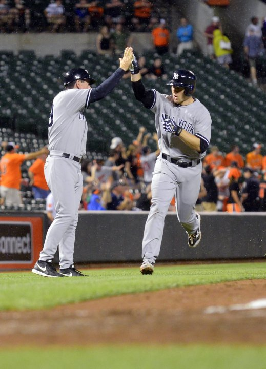 New York Yankees batter David Adams gets congratulations from third base coach Rob Thomson after hitting a solo home run the ninth inning of their MLB American League baseball game in Baltimore
