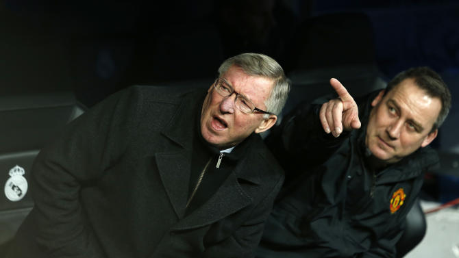 Manchester United's manager Sir Alex Ferguson, left, takes his seat ahead of the Champions League round of 16 first leg soccer match between Real Madrid and Manchester United at the Santiago Bernabeu stadium in Madrid, Wednesday Feb. 13, 2013. (AP Photo/Andres Kudacki)