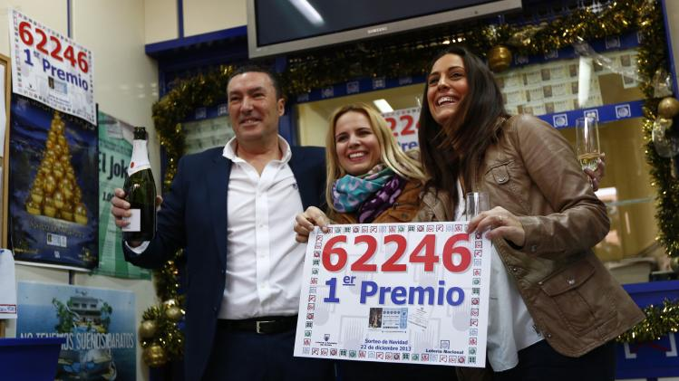 "Lottery shop employees hold a bottle of champagne and show a poster of the winning number to the first prize of ""El Gordo"" in a lottery shop where the number was sold in Sanlucar la Mayor"