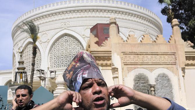 """A member of Egypt's April 6 Youth Movement shouts anti-Muslim brotherhood slogans as he wears a hat with pictures of victims of recent clashes with Arabic reading, """"the Brotherhood's terrorism"""", in front of the presidential palace in Cairo, Egypt, Saturday, April 6, 2013. The group is rallying Saturday to mark its fifth anniversary and to protest against President Mohammed Morsi.  (AP Photo/ Amr Nabil)"""