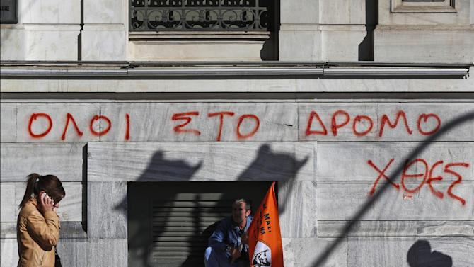 "A municipal worker participating in a anti-austerity rally sits in front of the National Bank of Greece building, underneath graffiti reading in Greek ""All to the streets yesterday"", in central Athens, Friday, Nov. 9, 2012. Cash-strapped Greece will issue short term debt on Tuesday in the hope of raising enough money to repay a key bond days later. Greece is not expected to get its next batch of international rescue loans by Nov. 16, when it has to roll over 5 billion euros in three-month treasury bills. (AP Photo/Lefteris Pitarakis)"