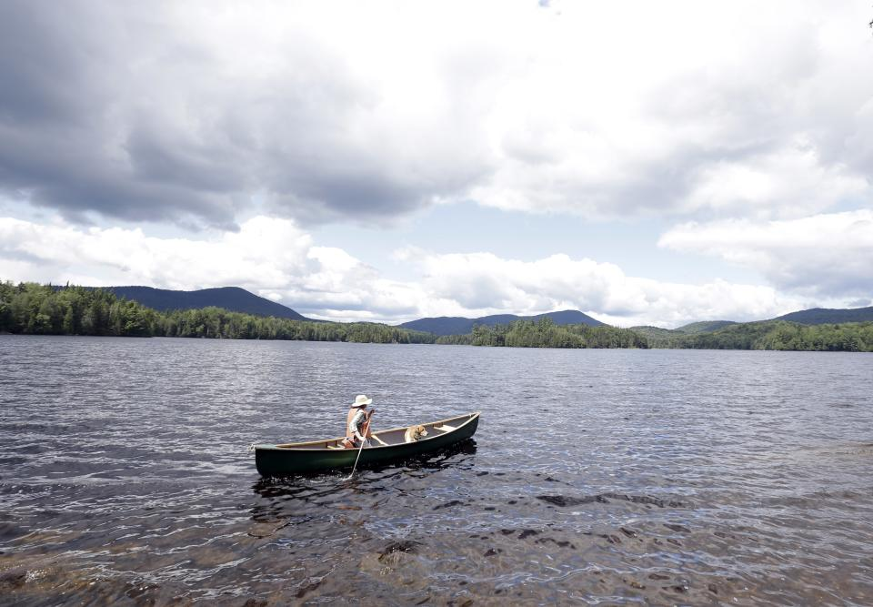 In this Tuesday, July 30, 2013 photo, Cynthia Taylor, of Watertown, Mass., canoes along the shoreline of Camp Santanoni on Newcomb Lake with her dog Arlo, in Newcomb, N.Y. Camp Santanoni is an Adirondack Mountain great camp that is being restored. (AP Photo/Mike Groll)