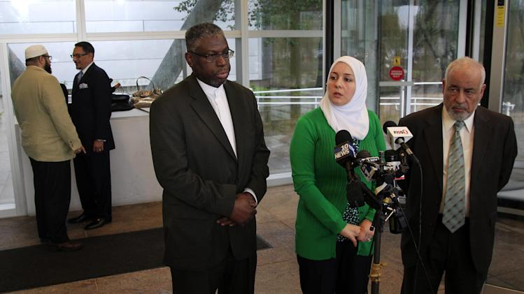 Imam Mustafa El-Amin, center, answers a question as he stands with Nadia Kahf, second right, attorney with the Council on American-Islamic Relations in New Jersey, and Mohamed Younes, right, of Passaic, in Trenton, N.J., Thursday, May 24, 2012, after a meeting between New Jersey Attorney General Jeffrey S. Chiesa and Muslim leaders. Mohamed El-Filali, left, of Paterson, and Imam Wahy-ud Deen Shareef, second left, of Irvington talk aside. Following a three-month review, Gov. Chris Christie's administration said Thursday that New York City police did not violate New Jersey laws when they conducted surveillance of Muslim businesses, mosques and student groups, rejecting demands by Muslim leaders for a formal investigation and a clampdown on cross-border police operations. Attorney General Chiesa, a Christie appointee, was meeting with Muslim leaders to discuss the findings. He said state officials and the New York Police Department have a new agreement to meet regularly to exchange information, and a new directive strengthens notification rules when New Jersey law enforcement learn of operations by outside agencies. (AP Photo/Mel Evans)