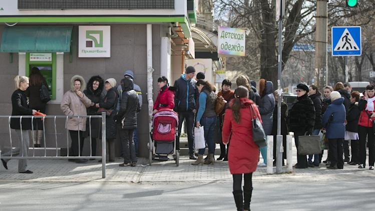 People queue to use an ATM after the bank imposed a limit of 1,500 hryvna ($150) on daily withdrawals in Simferopol, Ukraine, Thursday, March 13, 2014. Ukraine's largest bank says customers in the nation's Crimean Peninsula are lining up to withdraw cash from their accounts as the region occupied by Russian troops prepares for Sunday's referendum on joining Russia. (AP Photo/Vadim Ghirda)