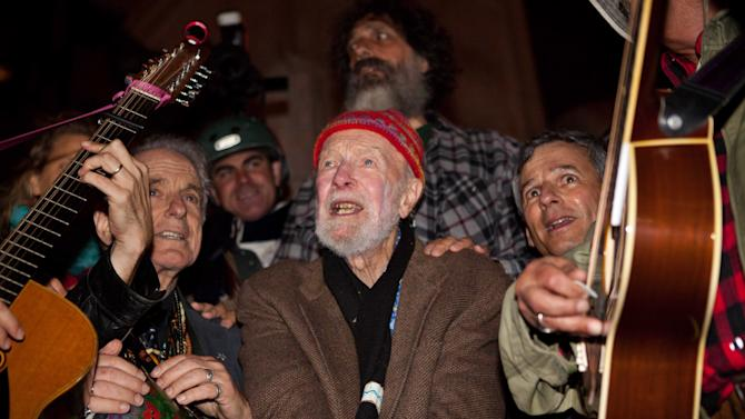 "Activist musician Pete Seeger, 92, center, sings before a crowd of nearly a thousand demonstrators sympathetic to the Occupy Wall Street protests at a brief acoustic concert in Columbus Circle, Saturday, Oct. 22, 2011, in New York. The demonstrators marched down Broadway singing ""This Little Light of Mine"" and other folk and gospel songs while ad-libbing lines about corporate greed and social justice. (AP Photo/John Minchillo)"
